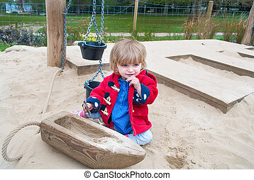 Baby in a sand pit - An eighteen month old baby girl playing...
