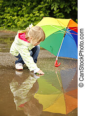 girl with an umbrella in the rain - little girl with an...