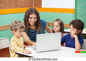 Teacher And Students Using Laptop In Class - Beautiful...