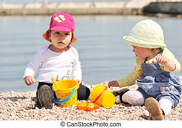 two playing baby girls on the beach