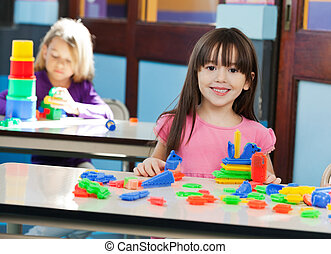 Girl With Construction Block While Friend Playing In...
