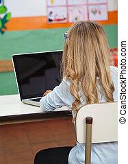 Little Girl Using Laptop In Preschool - Rear view of little...