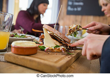 Businessman Having Burger With Colleagues - Cropped image of...