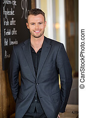 Young Businessman Standing In Restaurant - Portrait of young...