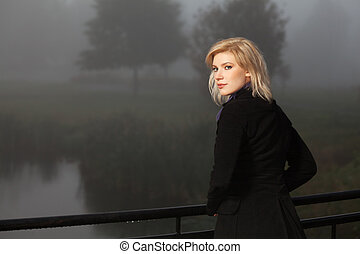 Young woman against a morning foggy landscape