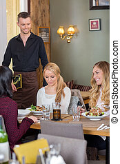 Female Friends With Food On Table While Waiter Holding Menu...
