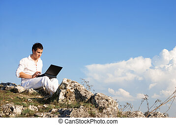 Wireless communication - Young man using his laptop, sitting...