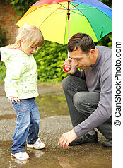 girl with an umbrella in the rain with his father - little...