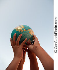 Hands holding up a globe .