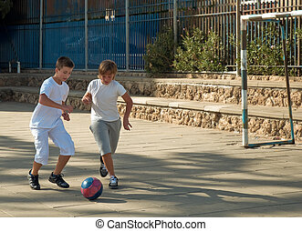 Two boys  playing football.