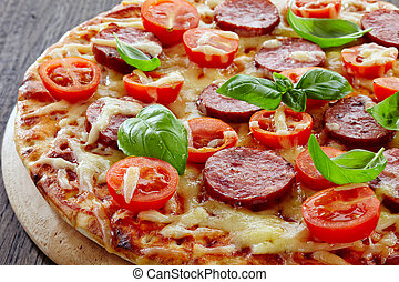 Salami and tomato pizza on wooden cutting board