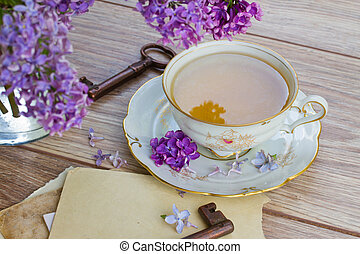 summer cup of tea with lilac and vintage photos