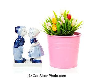 Typical Dutch souvenir in Delft blue and plastic tulips in bucket over white background
