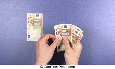 distributing 50 euros banknotes - man hand distributing 50...