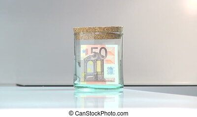 glass moneybox - man hand inserting and taking euro...