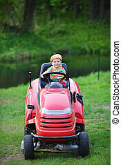 little boy riding a tractor on the lawn