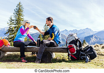 Couple hikers camping and drinking in mountains - Man and...