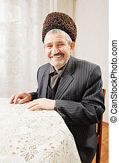 Happy senior man sitting at table - Happy senior man in...