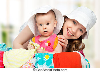 Mom and baby girl with suitcase baggage and clothes ready...