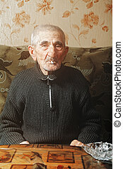 Senior man smoking while sitting on sofa at table