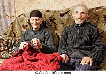 Senior spouses - Senior couple sitting on sofa woman...