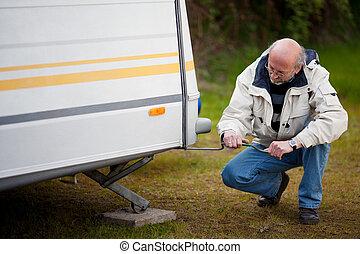 Senior Man Crouching While Repairing Caravan - Full length...