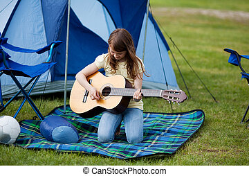 Girl Playing Guitar Against Blue Tent - Young girl playing...