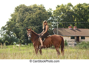 Young girl and chestnut horse portrait near the barn in...
