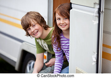 Two Kids Sitting In Doorway Of RV - Young brother and sister...
