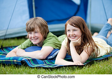 Two Kids Lying On Blanket With Tent In Background - Portrait...