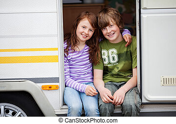 Boy And Girl In A Caravan - Young smiling girl and boy in a...