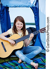 Young Girl Playing Guitar Against Tent - Young smiling girl...
