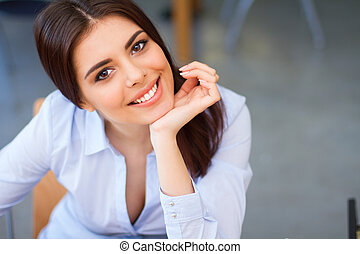 Closeup portrait of a young happy woman in blue shirt