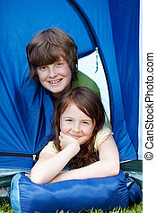 Brother And Sister Lying In Tent At Forest - Portrait of...