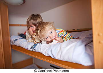 Young Boy With Brother Lying On Bunk Bed - Portrait of happy...