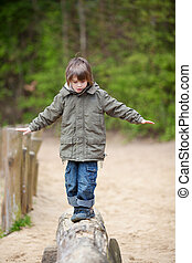 Boy In Jacket Walking On Wood At Park - Little boy in jacket...