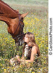 Girl sitting on the ground and chestnut horse standing near...