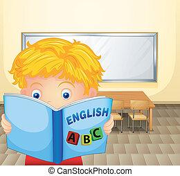 A boy reading a book inside the classroom
