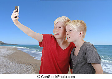 Two boys doing a selfie on the beach