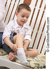 Adorable Boy Puts Socks On - Adorable Young Boy Getting...