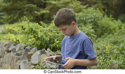 Boy using a tablet computer in a pa