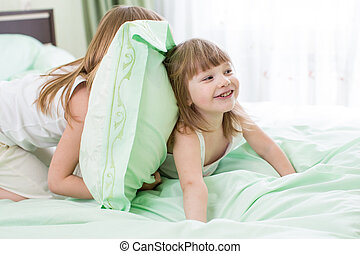 two girls playing in bed