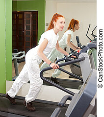 The young sporting woman in fitness center trains on a racetrack