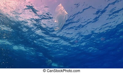 Plastic bag floating in ocean, pollution environment
