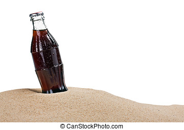 glass bottle of cola in the sand isolated on white...