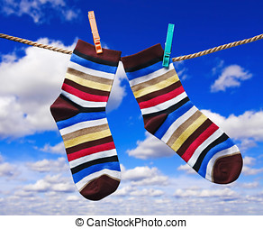 colorful socks hanging on clothespins against the sky with...