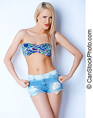 Blond sexy woman in short jeans and bikini bra posing over...