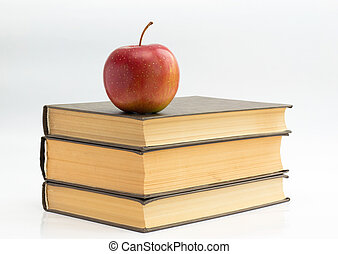 Knowledge - Stack of books in the green cover and red apple