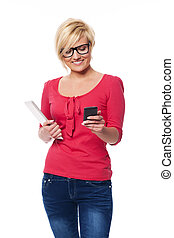 Fashion female using mobile phone and holding digital tablet...