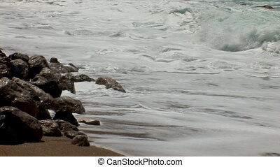 surf waves - surf lapping at the rocky shore